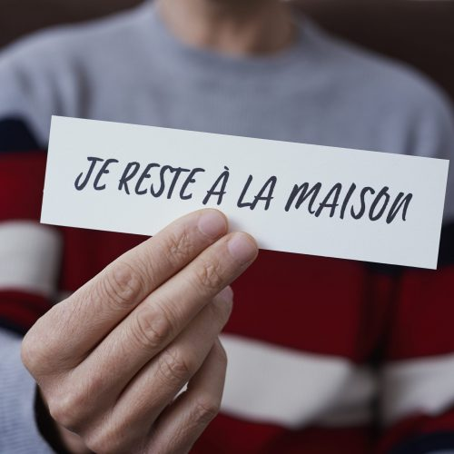 closeup of a man, in casual wear indoors, showing the message I stay at home in french written in a piece of paper, as a measure to stop the spreading of the covid-19